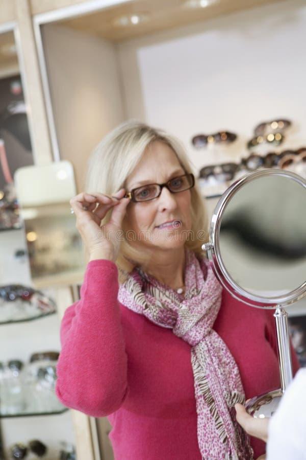 Vetri di prova della donna senior mentre esaminando specchietto in deposito fotografia stock