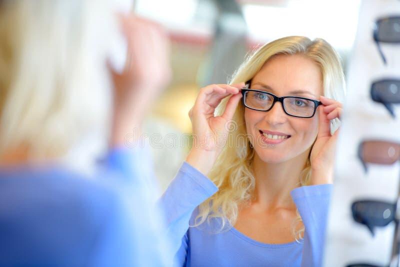 Vetri di prova della giovane donna attraente all'ottico immagini stock