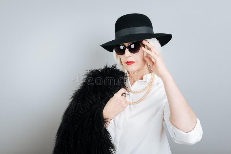 Vetri di sole commoventi della donna senior seria immagine stock