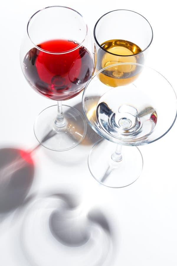 Vetri di vetro con le bevande dei colori differenti su un fondo bianco Vista superiore Il concetto di un cocktail alcolico fotografie stock