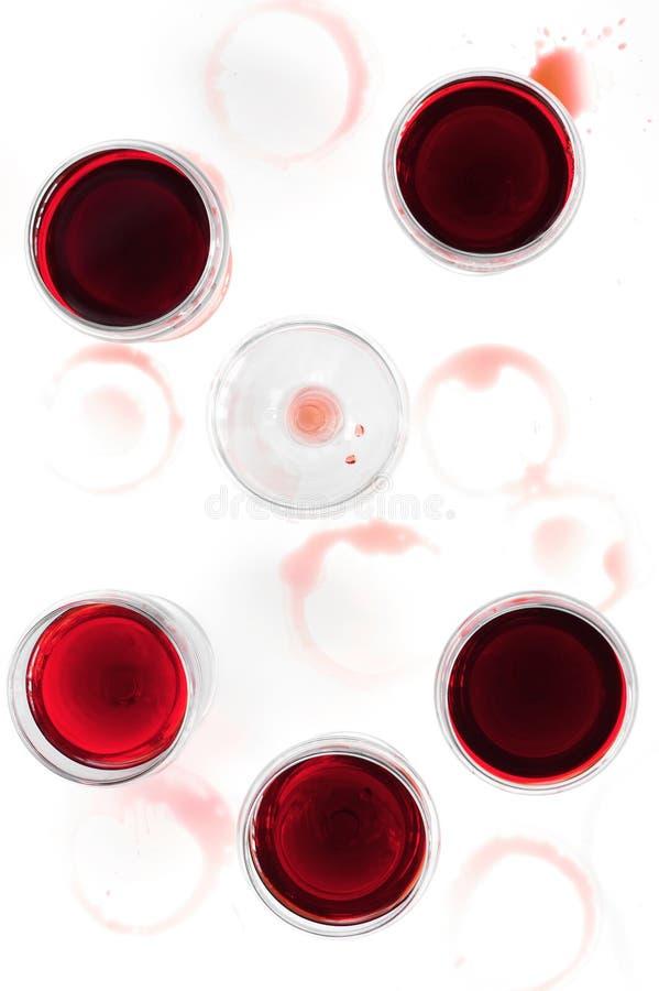 Vetri di vino con vino rosso sulla tavola macchiata immagine stock
