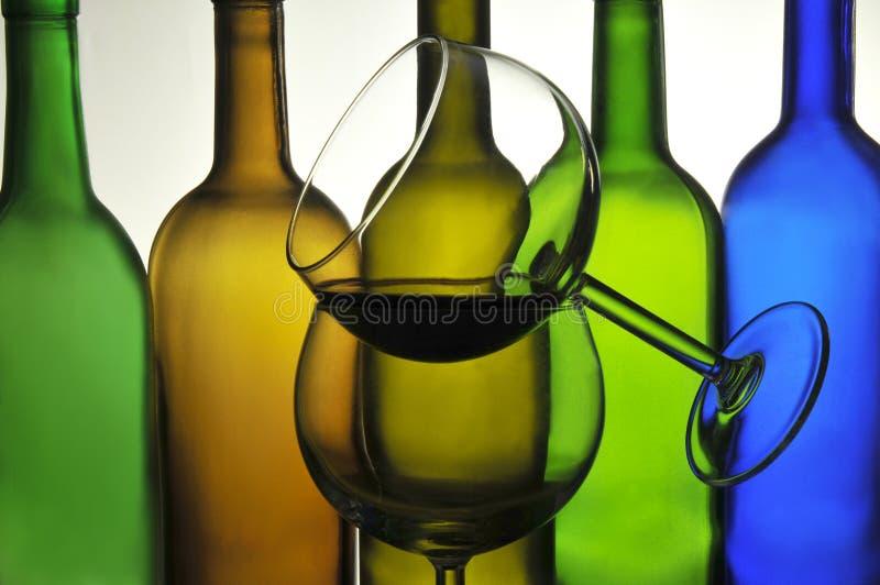 Vetri di vino davanti alle bottiglie fotografia stock libera da diritti