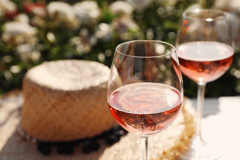 Vetri di vino rosato sulla tavola bianca in giardino di fioritura, primo piano Spazio per fotografie stock libere da diritti
