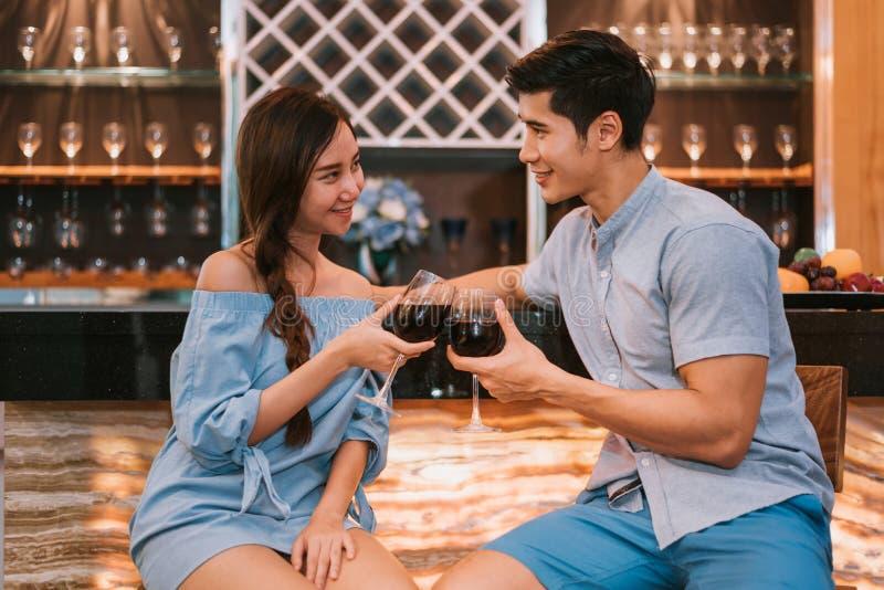 Vetri di vino tintinnanti delle giovani coppie asiatiche alla barra domestica del lux immagine stock libera da diritti