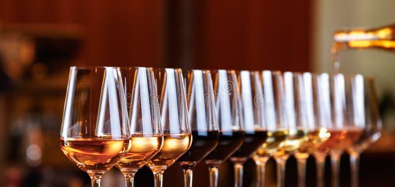 Vetri di vino in una fila Vino di versamento E r fotografia stock