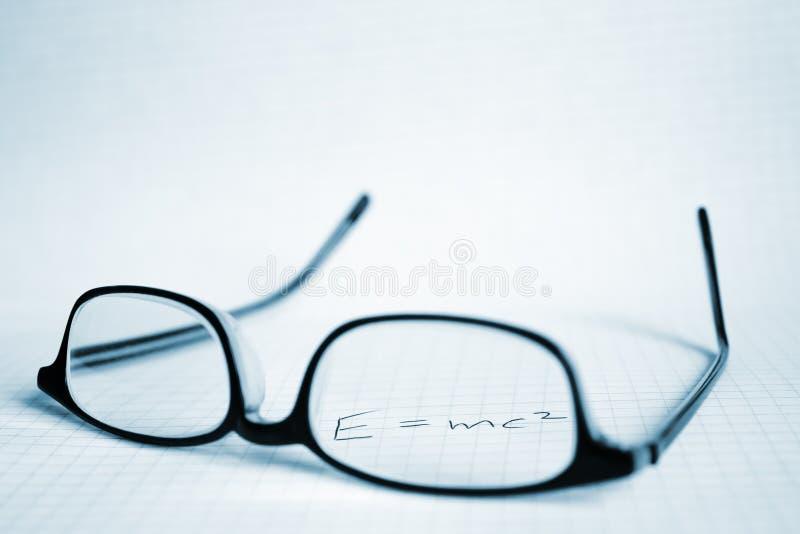 Vetri e documento con E=mc2 fotografia stock