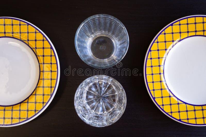 Vetri e piatti vuoti su fondo di legno nero fotografie stock libere da diritti