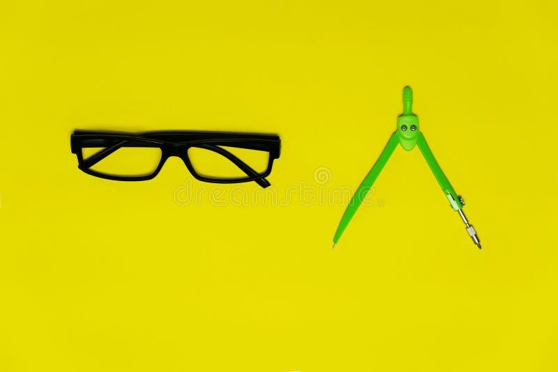 Vetri neri e compasess verdi variopinti per il cerchio che assorbe scuola o il fondo giallo variopinto di istruzione fotografia stock