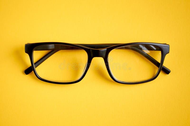 Vetri neri sulla composizione gialla nel fondo, occhiali fotografia stock