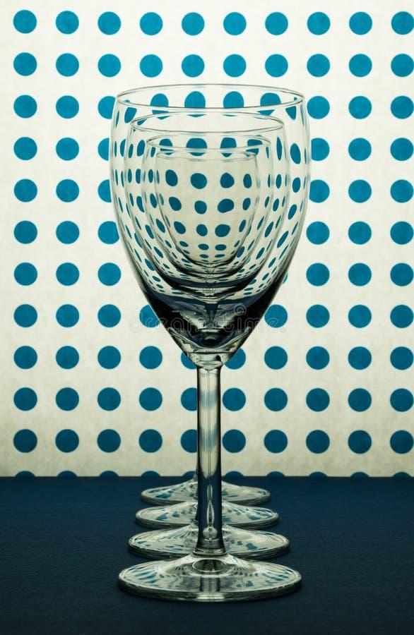 Vetri per vino che sta nella linea e nel fondo bianco con i punti blu immagine stock