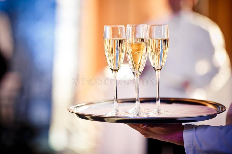 Vetri pieni di champagne sul vassoio fotografia stock