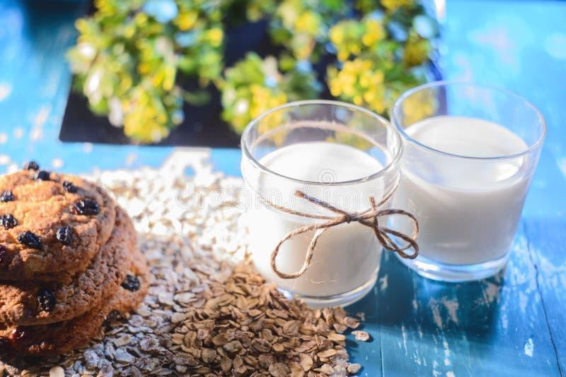 Vetri riempiti di farina d'avena con i biscotti, in uno stile rustico su un fondo floreale fotografie stock
