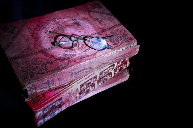 Vetri stessi degli occhi degli occhiali del primo piano vecchi sul libro rosso molto vecchio che si trova sullo specchio per la r immagine stock