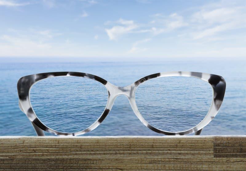 Vetri su una tavola di legno davanti al mare immagini stock libere da diritti