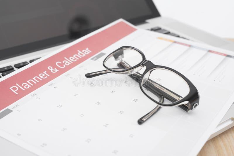 Vetri sulla riunione del pianificatore del calendario sull'ufficio dello scrittorio organizzazione fotografia stock libera da diritti