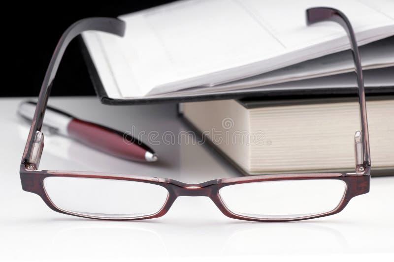 Vetri, taccuino e libro di lettura. immagine stock
