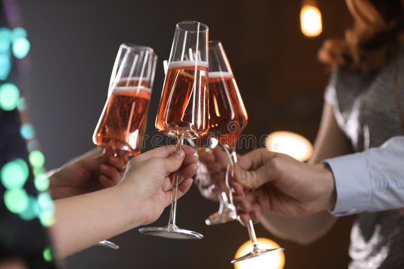Vetri tintinnanti degli amici con champagne su fondo vago fotografie stock