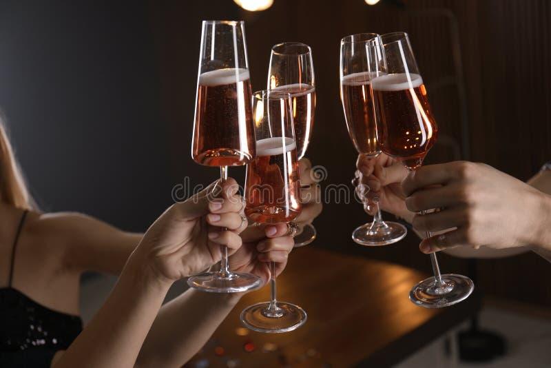 Vetri tintinnanti degli amici con champagne su fondo vago fotografie stock libere da diritti
