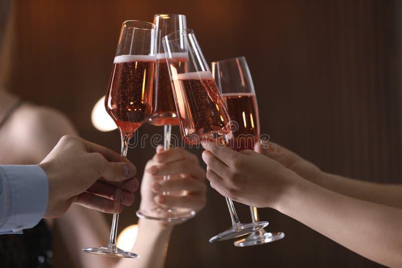 Vetri tintinnanti degli amici con champagne su fondo vago immagini stock libere da diritti