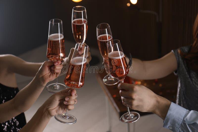 Vetri tintinnanti degli amici con champagne su fondo vago immagine stock