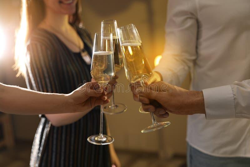 Vetri tintinnanti degli amici di champagne al partito fotografia stock libera da diritti