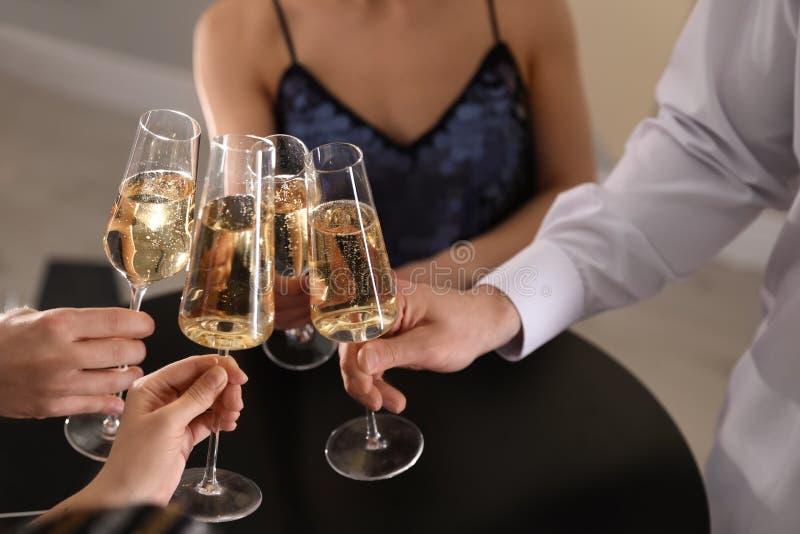 Vetri tintinnanti degli amici di champagne in ristorante fotografia stock libera da diritti