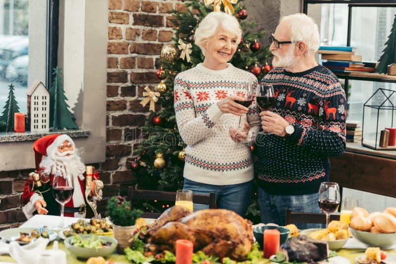 vetri tintinnanti delle belle coppie senior sulla notte di Natale immagini stock