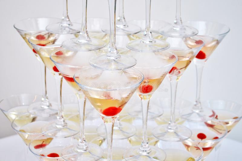 Vetri triangolari di martini, con le ciliege e l'azoto liquido, creare vapore, costruito sotto forma di una piramide fotografia stock