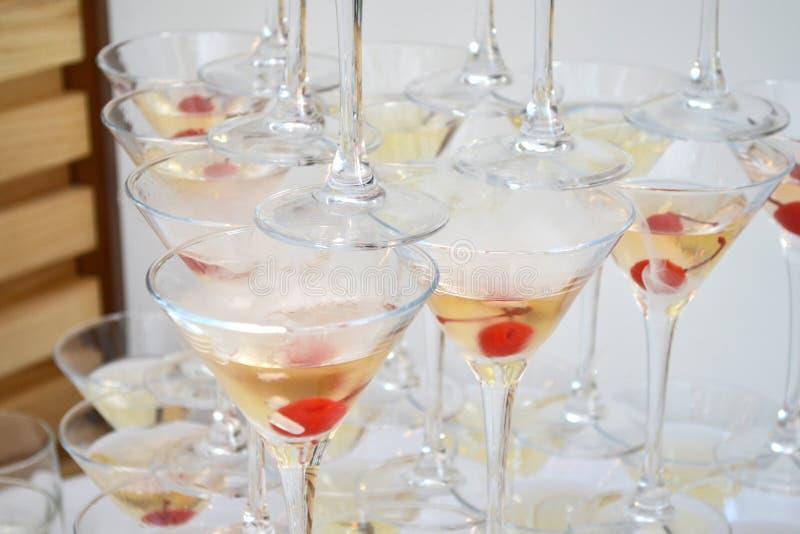Vetri triangolari di martini, riempiti di champagne con le ciliege e l'azoto liquido, creare vapore, forma di una piramide immagini stock libere da diritti