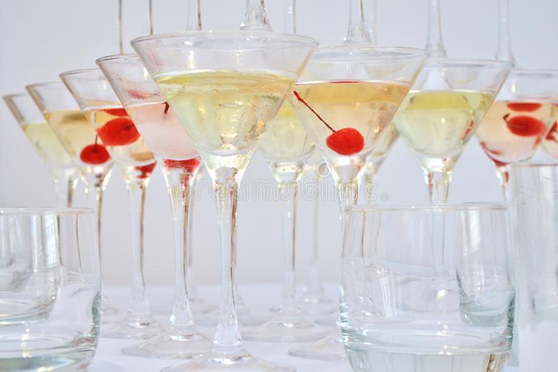 Vetri triangolari di martini, riempiti di champagne con le ciliege e l'azoto liquido, creare vapore, forma di una piramide fotografia stock