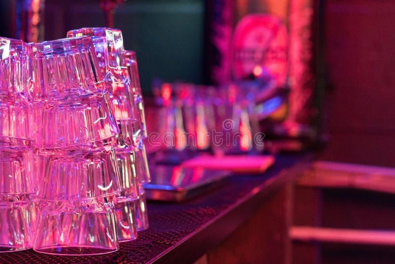 Vetri vuoti sulla tabella I vetri per un cocktail hanno riflesso nella superficie lucida della tavola fotografia stock libera da diritti
