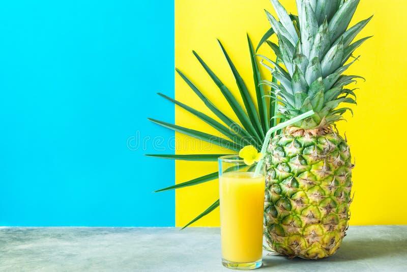 Vetro alto con la noce di cocco arancio di recente urgente Juice Straw Flower dell'ananas Foglia di palma rotonda su fondo giallo immagini stock