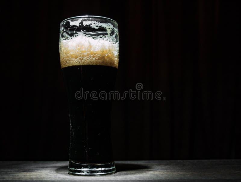 Vetro alto di birra scura sopra un fondo scuro immagini stock