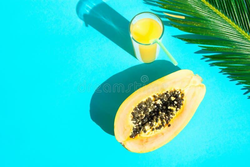 Vetro alto di disposizione della composizione piana in disposizione con il fondo fresco di Juice Papaya Palm Leaf Blue della frut immagine stock libera da diritti