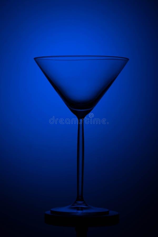 Vetro alto vuoto di martini sul nero e su un fondo blu immagini stock libere da diritti