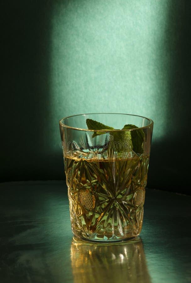 Vetro antiquato con la bevanda dell'alcool e pezzo di menta contro la parete verde Luce bassa e attutita fotografie stock