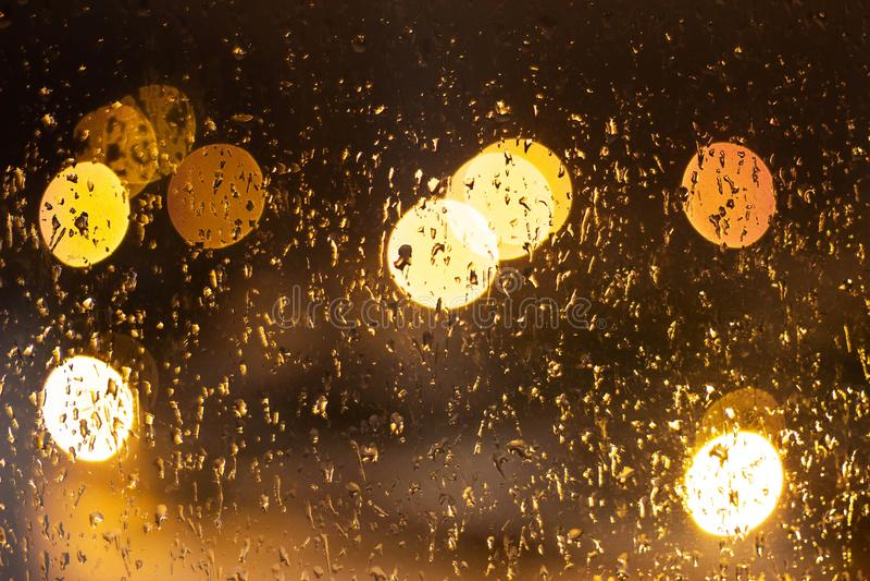 Vetro bagnato con le gocce e la luce dalle lampade, fondo, notte immagine stock libera da diritti