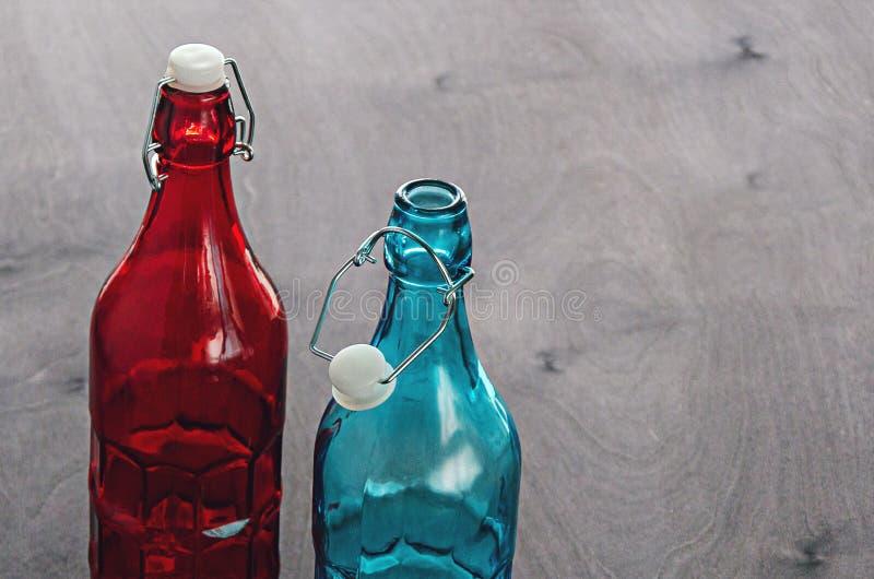 Vetro blu e rosso colorato delle bottiglie, con un tappo dentato sul collo, su un ripiano del tavolo di legno fotografia stock