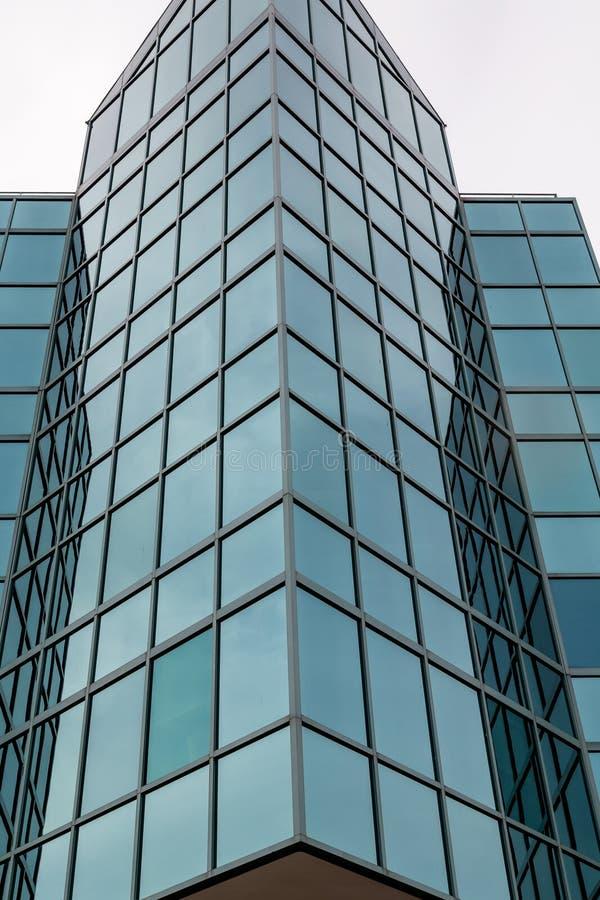 Vetro blu inclinato sulla torre dell'ufficio fotografie stock libere da diritti
