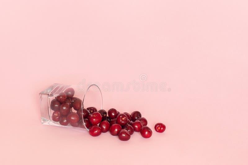 Vetro caduto con la ciliegia matura rossa sparsa su fondo rosa Concetto di succo naturale fresco, frullati, cibo sano o fotografia stock libera da diritti