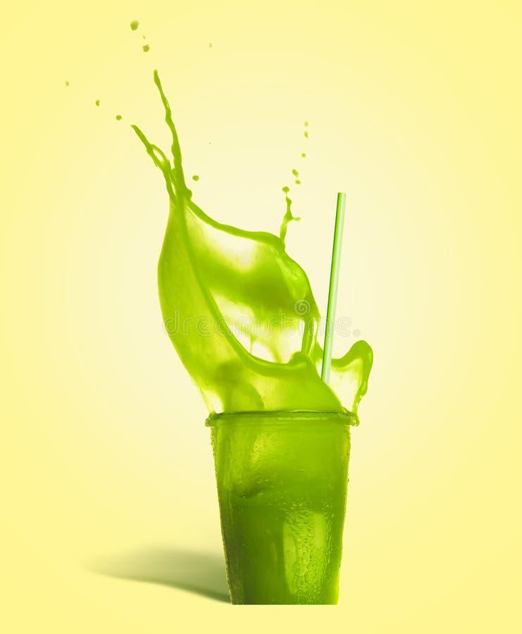 Vetro con cannuccia e la bevanda verde di estate della spruzzata: frullato o succo su fondo giallo immagini stock libere da diritti
