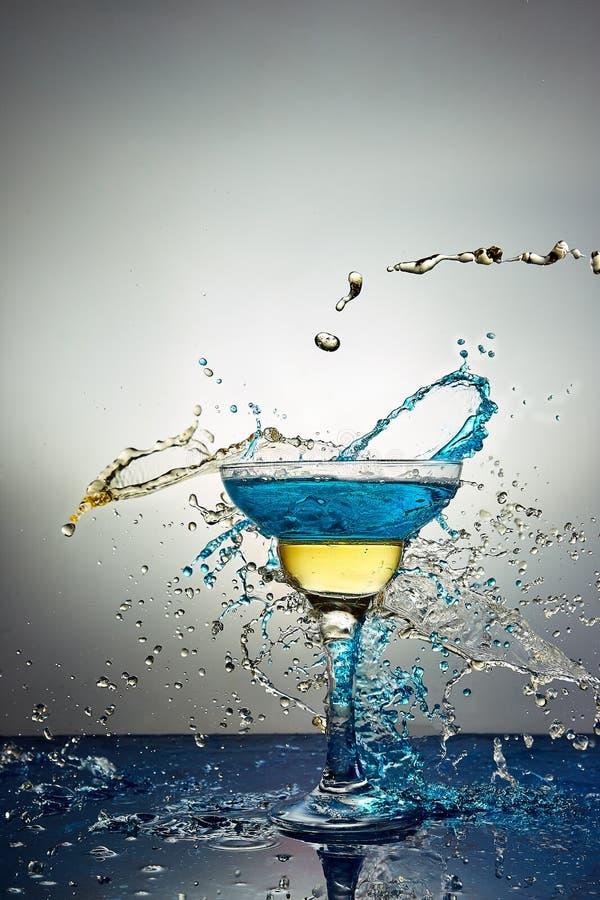 Vetro con champagne o il cocktail blu e giallo levitazione fotografia stock libera da diritti