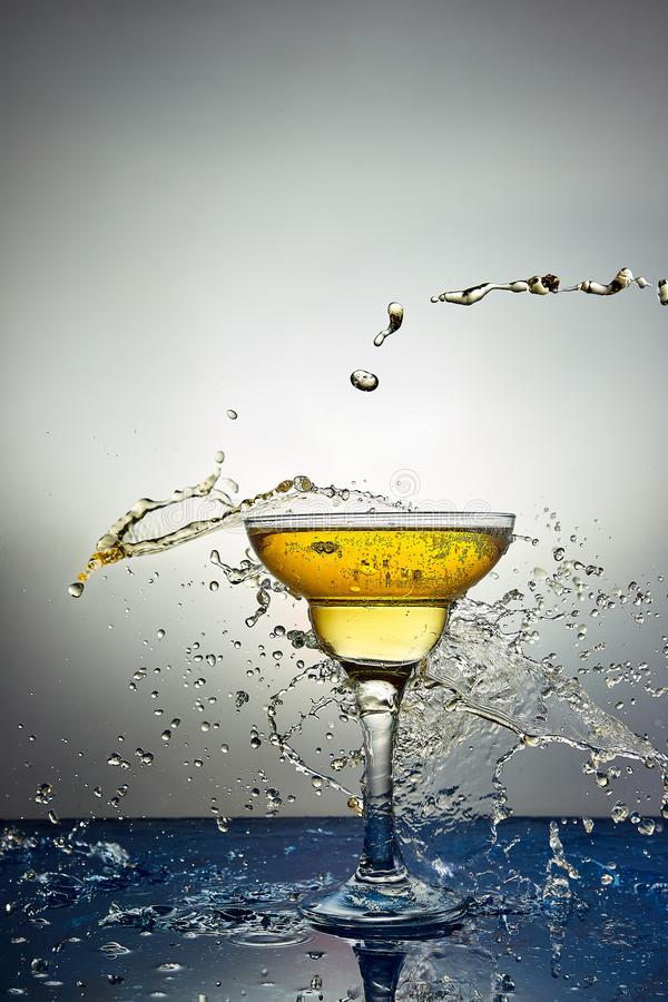 Vetro con champagne o il cocktail giallo levitazione immagini stock libere da diritti
