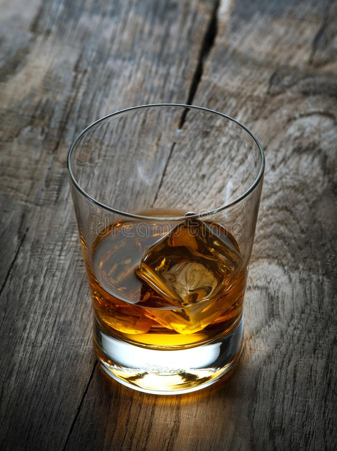 Vetro con ghiaccio e whiskey su fondo di legno immagine stock libera da diritti