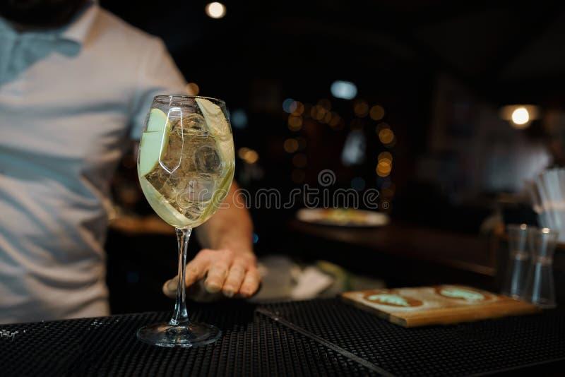 Vetro con i supporti dolci del vino bianco nel club sul contatore della barra contro lo sfondo del barista in una maglietta bianc immagine stock