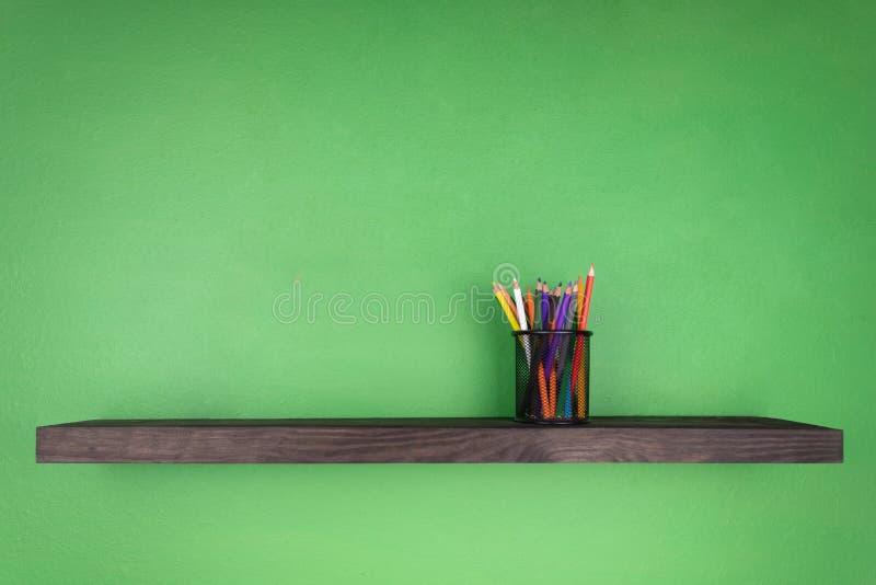 Vetro con le matite messe su uno scaffale scuro con struttura di legno su un fondo verde immagine stock
