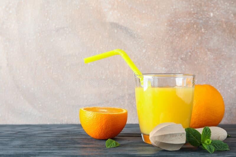 Vetro con succo d'arancia e tubulo fresco, arance, menta e spremiagrumi di legno sulla tavola di legno contro il fondo di colore fotografia stock