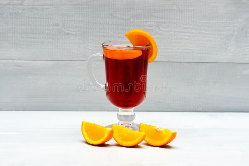 Vetro con vin brulé vicino a frutta arancio succosa Vin brulé rosso caldo isolato su fondo bianco con le spezie di natale fotografia stock libera da diritti