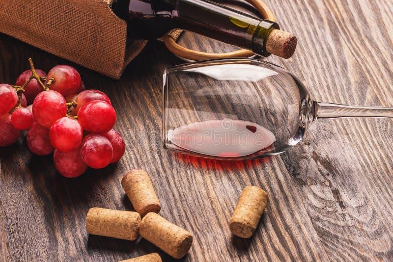 Vetro con vino, una bottiglia ed il mazzo di uva matura, fondo di legno immagine stock libera da diritti