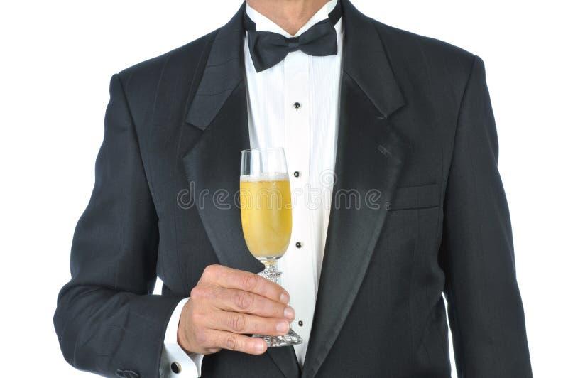 Vetro da portare della holding dello smoking dell'uomo di Champagne fotografia stock libera da diritti